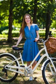 Femme vue de face posant avec son vélo