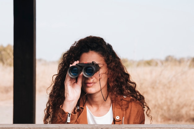 Femme vue de face à la recherche à travers des jumelles