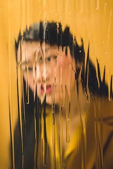 Femme vue de face en regardant la caméra derrière une fenêtre humide