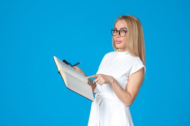Femme vue de face en robe blanche posant avec un bloc-notes sur une autorité de travail bleue