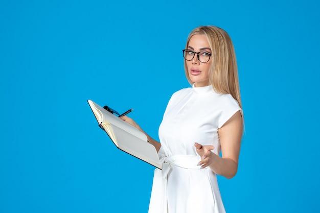 Femme vue de face en robe blanche posant avec un bloc-notes sur un travail bleu