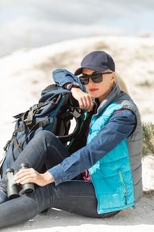 Femme vue de face avec sac à dos et jumelles