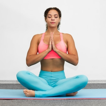 Femme vue de face se détendre sur un tapis de yoga