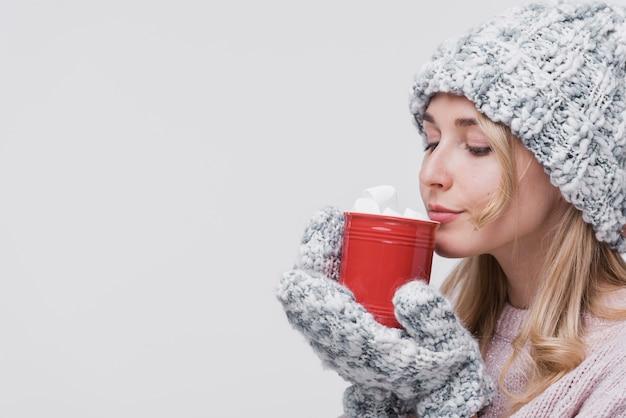 Femme vue de face avec une tasse rouge