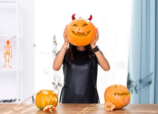 Femme vue de face tenant une citrouille sculptée pour halloween