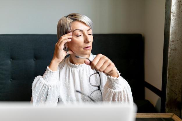 Femme vue de face tenant des lunettes