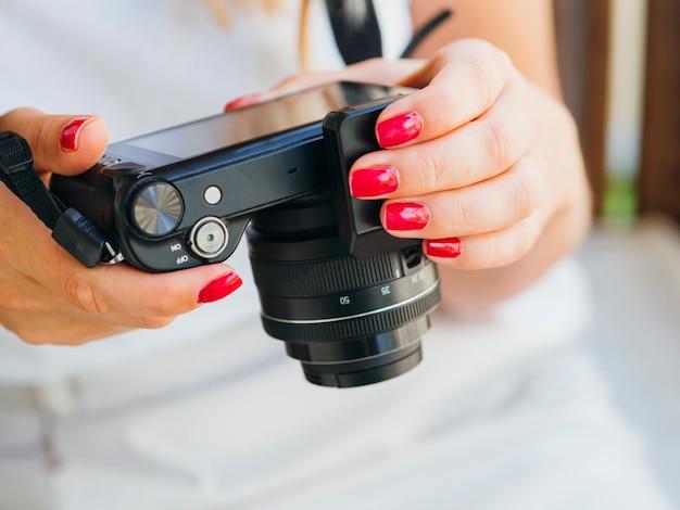 Femme vue de face vérifiant l'appareil photo