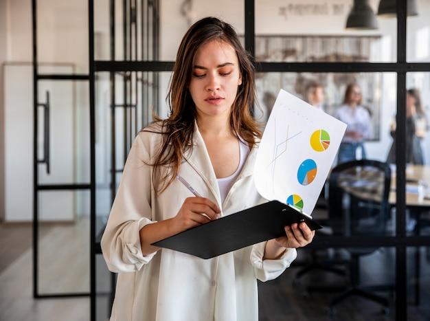 Femme vue de face vérifiant les résultats de l'entreprise