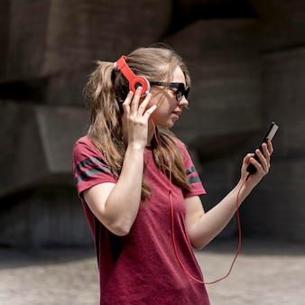 Femme vue latérale, à, lunettes soleil, écoute, musique