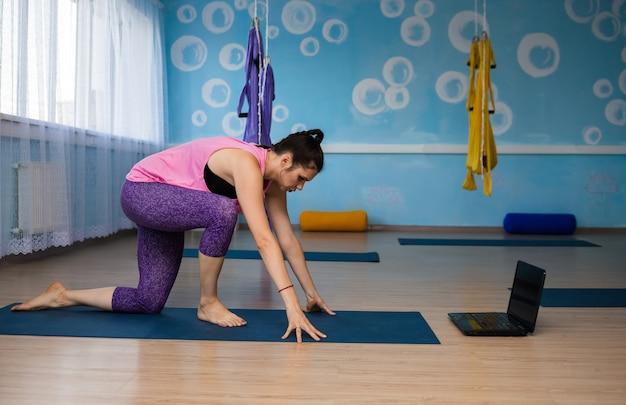 Une femme yoga pratique à distance avec un ordinateur portable dans la salle de sport