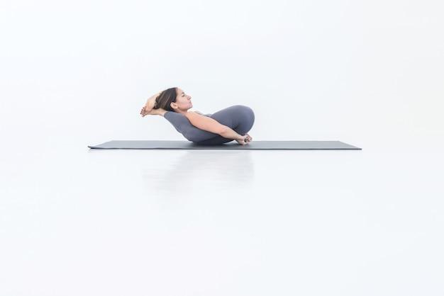 Femme yogi faisant du yoga allongée sur le dos sur un tapis avec les jambes derrière la tête, pose relaxante