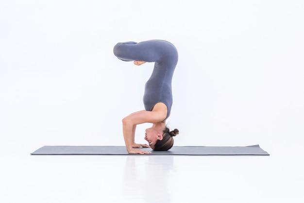 Femme yogi faisant du yoga sur un tapis debout dans une pose sur une montagne dans un lotus
