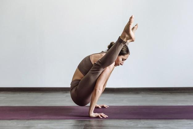 Femme yogi faisant pose de luciole en yoga sur tapis dans la chambre