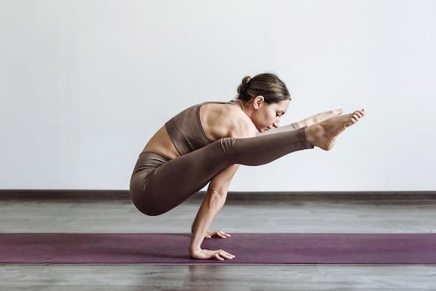 Femme yogi faisant pose de luciole en yoga sur tapis