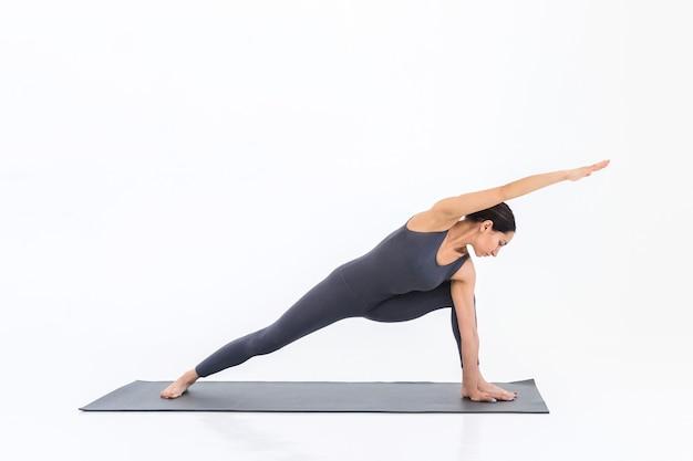 Femme yogi pratiquant le yoga sur le tapis sur un fond blanc. dame faisant des étirements