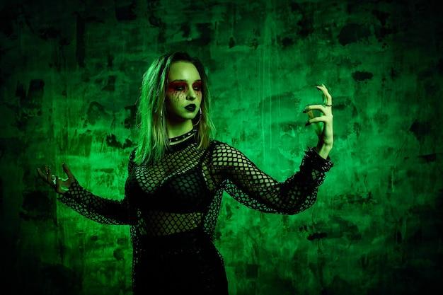 Femme zombie en tenue d'halloween posant avec sur fond vert. une fille magnifique en vêtements célèbre le jour des morts. concept d'halloween, costume de sorcière, couleurs vives, steam punk.