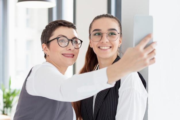 Femmes adultes prenant un selfie au bureau