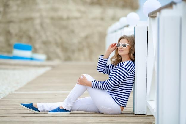 Les femmes adultes de race blanche s'asseoir sur la plage rocheuse avec un foulard bleu se détendre et penser à quelque chose.