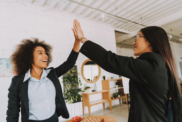 Les femmes d'affaires asiatiques et afro s'en donnent cinq.