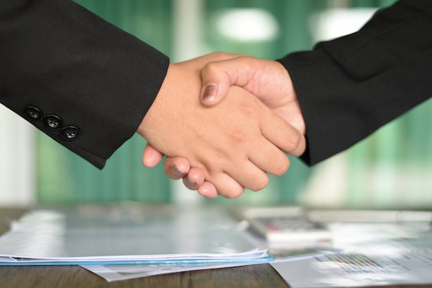 Des femmes d'affaires asiatiques qui réussissent serrent la main à des personnes ayant besoin d'échange et de coopération