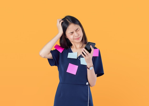 Femmes d'affaires asiatiques se sentant mal à la tête à cause du dur labeur et du regard prolongé sur leur smartphone, post note sur le corps, sur orange.