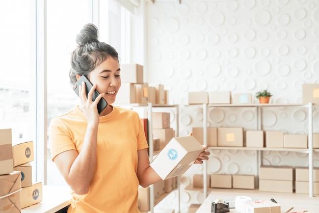 Femmes d'affaires asiatiques travaillant à la maison avec une boîte sur le lieu de travail