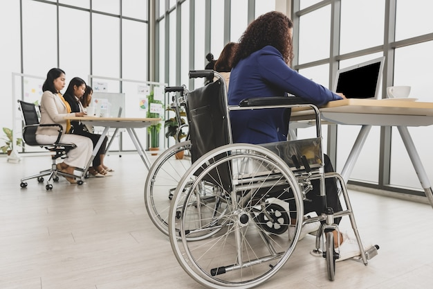 Femmes d'affaires asiatiques, y compris une femme handicapée assise sur un fauteuil roulant, travaillant dur sur un ordinateur portable sur la table au bureau. concept pour réunion d'affaires.