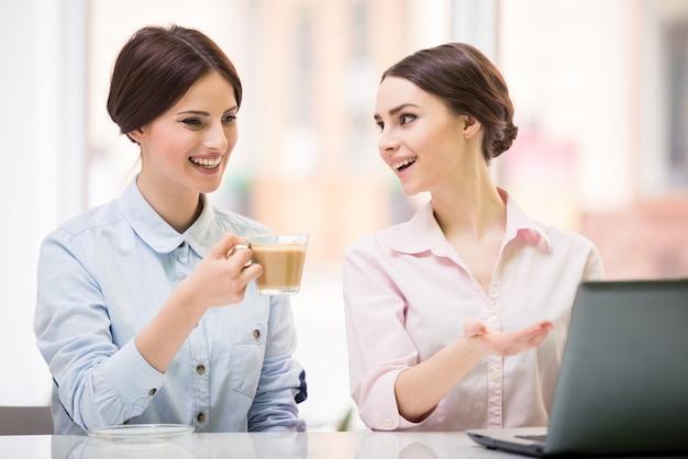 Femmes d'affaires assis dans un café urbain et utilisant un ordinateur portable.