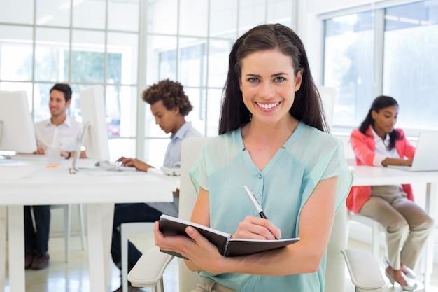 Femmes d'affaires attrayantes écrivant dans le cahier avec des collègues derrière elle