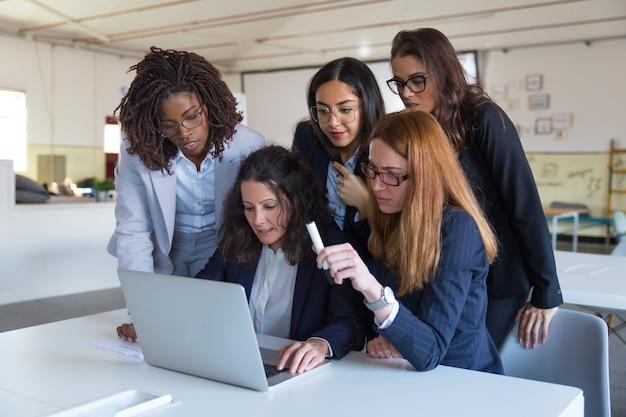 Femmes d'affaires concentrées utilisant un ordinateur portable au bureau
