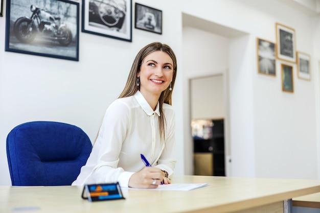 Femmes d'affaires dans le bureau d'inspection technique. une femme adulte est assise à une table devant un mur blanc et tient un crayon à la main tout en signant des papiers. service de voiture, signature de la documentation