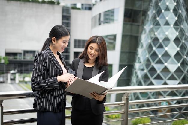 Les femmes d'affaires discutent de la paperasserie contre la balustrade. concept des entreprises.