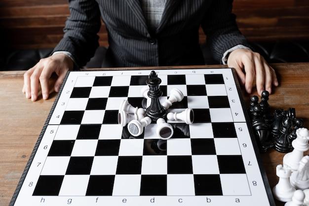 Les femmes d'affaires et les échecs avec fond en bois remettent en cause la stratégie commerciale au concept de réussite