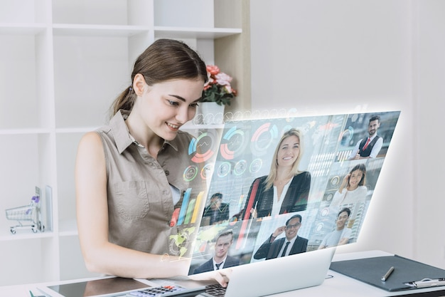 Femmes d'affaires heureuses d'utiliser une réunion en ligne de haute technologie via internet avec un appareil numérique futuriste pour passer des appels vidéo avec des partenaires commerciaux du monde entier dans le concept de bureau.