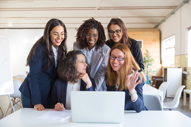 Femmes d'affaires heureux travaillant avec un ordinateur portable