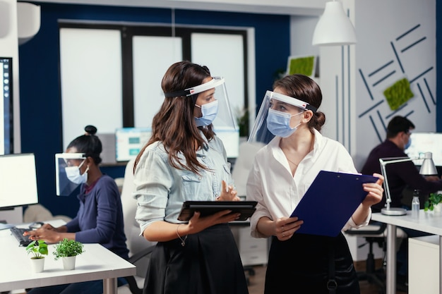 Femmes d'affaires avec des masques de protection contre le coronavirus debout sur le lieu de travail parlant des données financières de l'entreprise détenant une tablette numérique. équipe commerciale multiethnique travaillant dans le respect de la distance sociale
