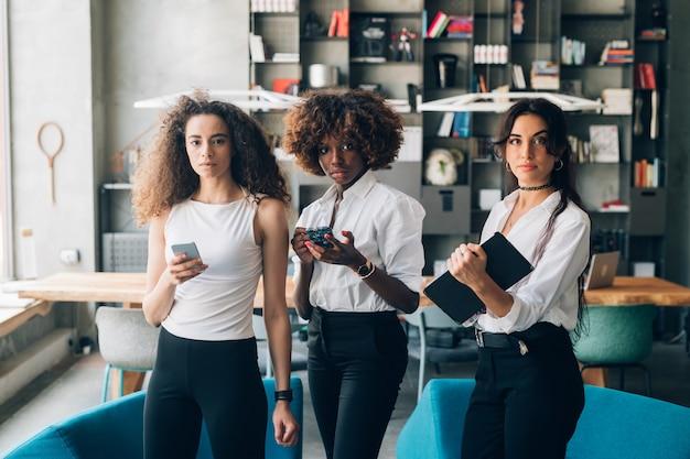 Femmes d'affaires multiculturelles debout avec appareil mobile dans un bureau de travail
