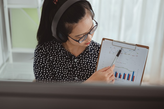 Les femmes d'affaires portant des écouteurs sans fil regardant un écran d'ordinateur ont une conversation agréable