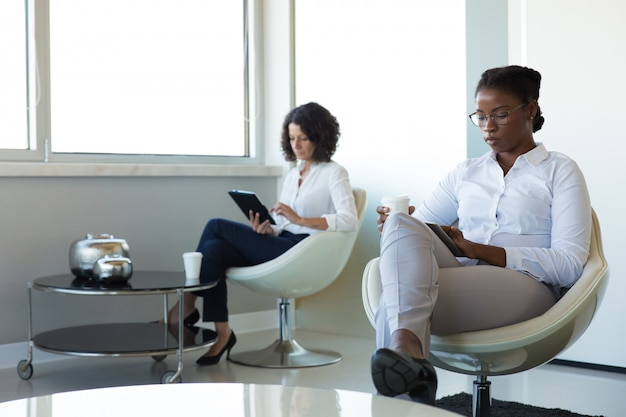 Femmes d'affaires profitant d'une pause de travail dans le salon du bureau