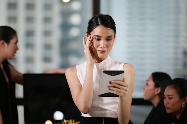 Femmes d'affaires à la recherche sur tablette contre collègue au bureau