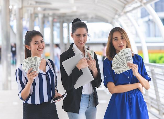 Femmes d'affaires riches comptant l'argent comptant dans leur main