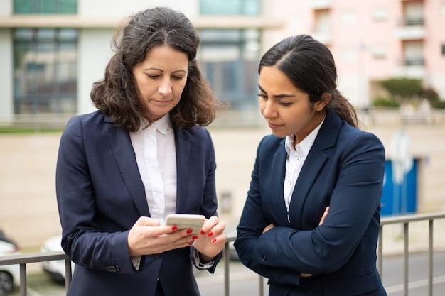Femmes d'affaires sérieuses utilisant un smartphone