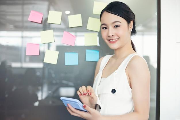 Femmes d'affaires souriant et travaillant ensemble sur le mur en verre avec poster autocollants.