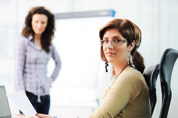 Femmes d'affaires tenant une conférence d'écriture sur un tableau dans un bureau