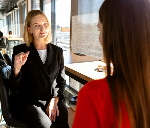 Les femmes d'affaires utilisant la langue des signes au travail pour communiquer entre elles