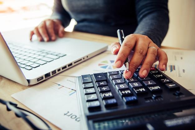 Les femmes d'affaires utilisent une calculatrice pour calculer le revenu de l'entreprise.