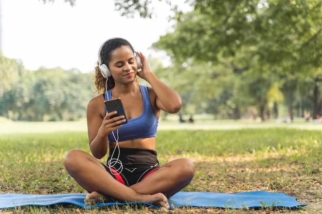 Femmes afro-américaines assis avec sourire heureux et écoutant la musique dans le parc pour se détendre