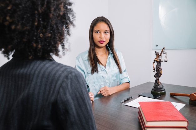 Femmes afro-américaines assis à table près de document, stylo, figure et marteau