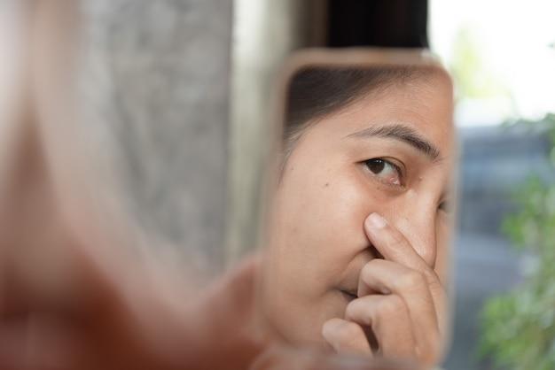 Les femmes d'âge moyen regardent le miroir pour voir les rides du visage