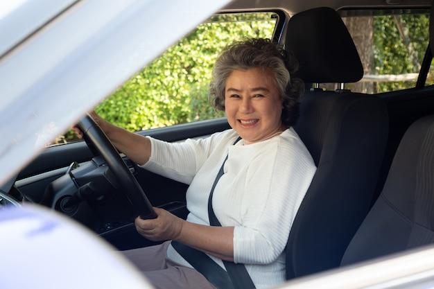 Femmes âgées asiatiques au volant d'une voiture et sourire joyeusement avec une expression positive heureuse pendant le trajet en voiture, les gens aiment le transport en riant et détendue femme mature heureuse sur le concept de roadtrip